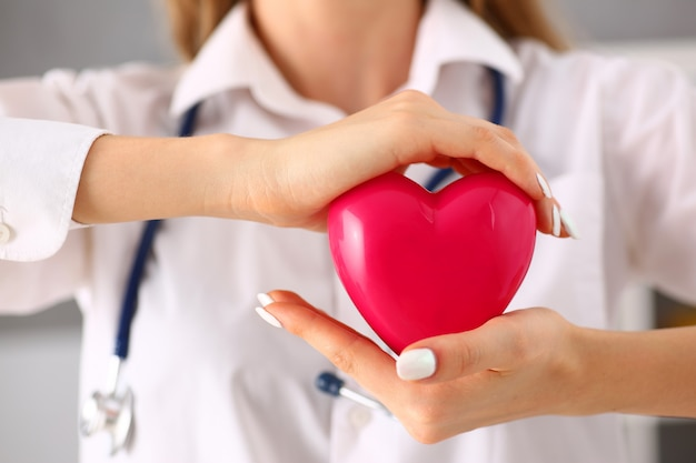 Kobiety lekarki chwyt w rękach i okładkowa czerwieni zabawka
