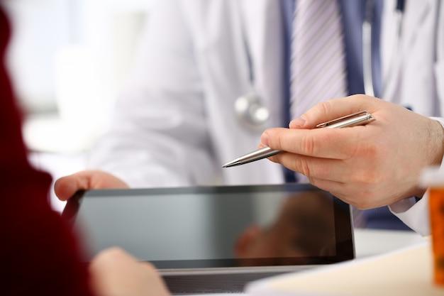 Kobiety lekarki ręki trzymają cyfrowego i pokazują