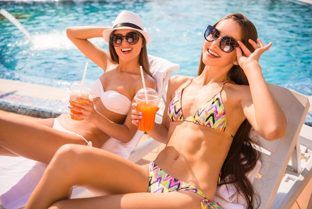 Kobiety leżą na szezlongu i piją koktajl.