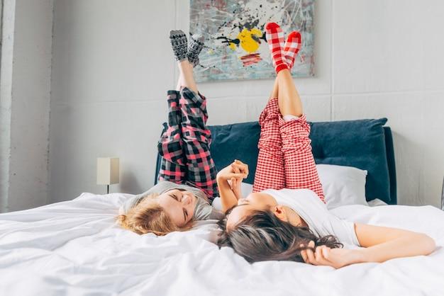 Kobiety leżące na łóżku trzymając się i krzyżując nogi