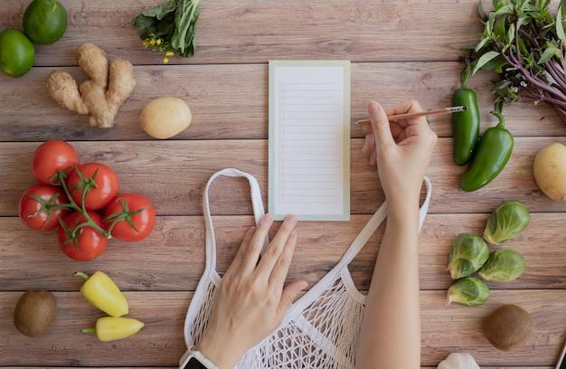 Kobiety lista na notatce dla weganinu zdrowego jedzenia na drewnianej powierzchni. darmowe zakupy spożywcze z tworzyw sztucznych. widok z góry. leżał płasko