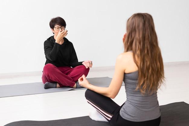 Kobiety medytujące i zakrywające nozdrze