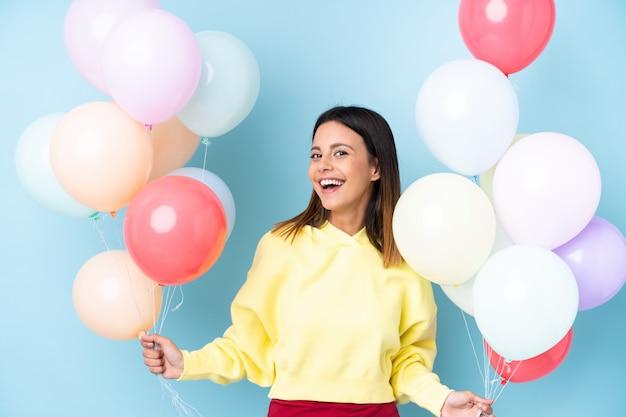 Kobiety mienia balony w przyjęciu nad błękit ścianą