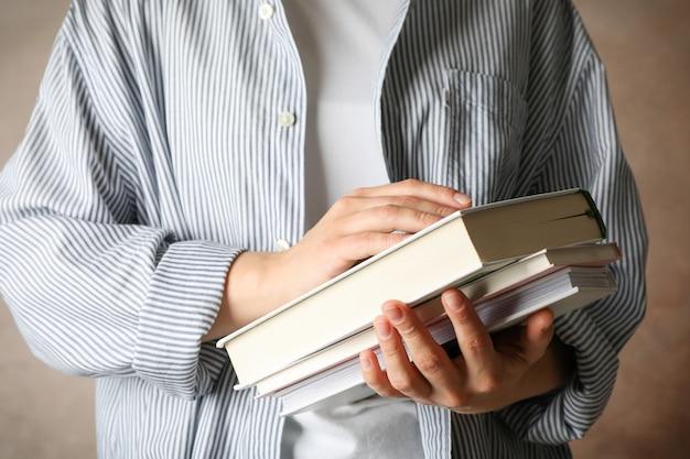 Kobiety mienia książki przeciw brąz przestrzeni, frontowy widok