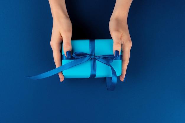 Kobiety mienia prezenta pudełko z faborkiem przeciw klasycznemu błękitnemu tłu, odgórny widok