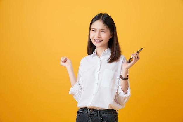 Kobiety mienia smartphone na żółtym tle