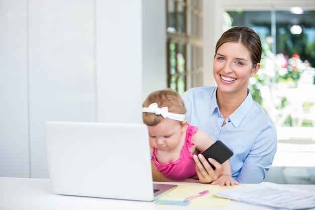 Kobiety mienia telefon komórkowy podczas gdy siedzący z dziewczynką