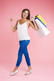 Kobiety mienia torba na zakupy patrzeje prosto odizolowywający na menchii ścianie