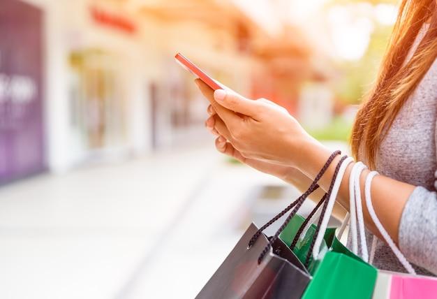 Kobiety mienia torba na zakupy robi online zakupy na jej telefonie komórkowym