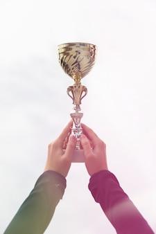 Kobiety mienia trofeum złocista filiżanka