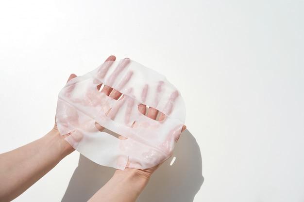 Kobiety mienie w ręki tkankowej twarzowej masce przygotowywającej używać na biel ścianie