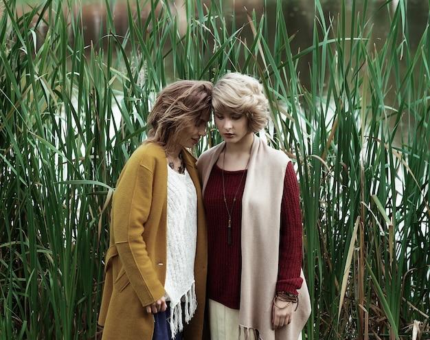 Kobiety moda pozowanie razem odkryty, jesienny park.