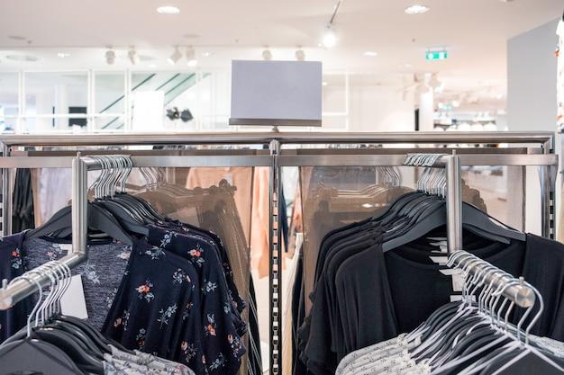Kobiety modne ubrania wiszące na szynie z ceną