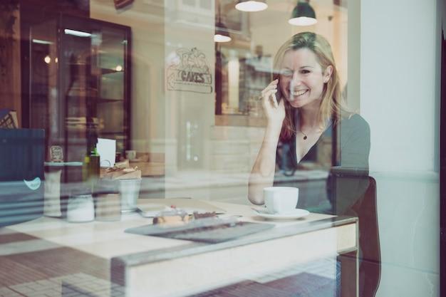 Kobiety mówienie na telefonie i patrzeć kamerę w kawiarni
