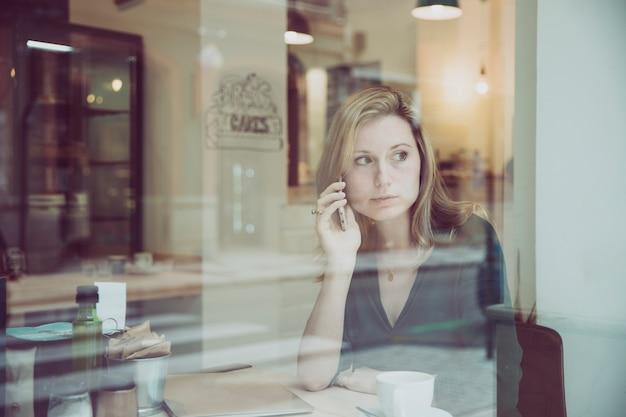 Kobiety mówienie na telefonie i przyglądającym okno w kawiarni out