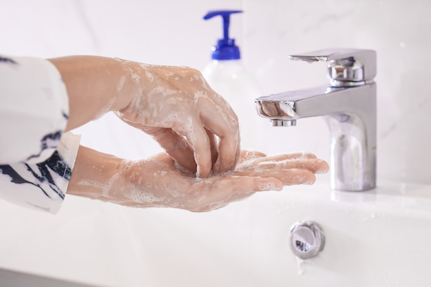 Kobiety myjące ręce antybakteryjnym środkiem dezynfekującym z mydłem lub żelem alkoholowym w celu zapobiegania wirusom corona covid-19 higiena, aby zatrzymać rozprzestrzenianie się zarazków i bakterii i uniknąć infekcji wirusem corona covid-19.