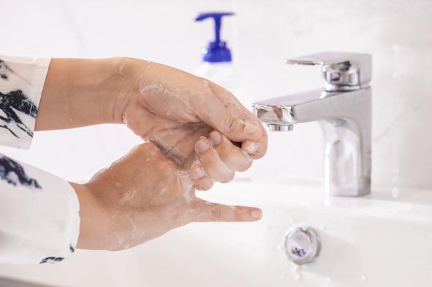 Kobiety myjące ręce antybakteryjnym środkiem dezynfekującym z mydłem lub żelem alkoholowym w celu zapobiegania wirusom corona covid-19