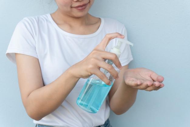 Kobiety myjące ręce żelem alkoholowym. zapobiegają rozprzestrzenianiu się zarazków i bakterii oraz unikają infekcji wirusem koronowym. koncepcja higieny