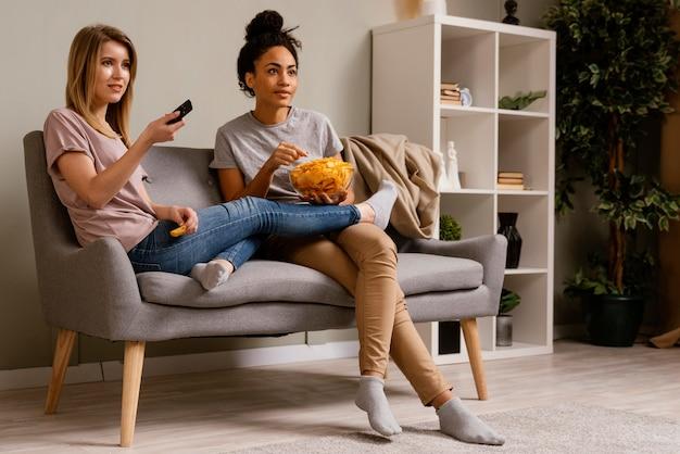 Kobiety na kanapie oglądając telewizję i jedząc frytki