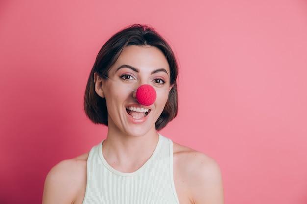 Kobiety na różowym tle całkiem zabawna i uśmiechnięta młoda kobieta ubrana w nos klauna, nastrój partii