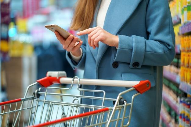 Kobiety nabywca z furą w przejściu do sklepu z listą sklepów spożywczych na smartfonie podczas zakupów żywności