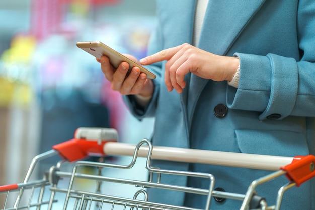 Kobiety nabywca z furą w przejściu supermarket z listą sklep spożywczy na smartphone podczas zakupy jedzenia