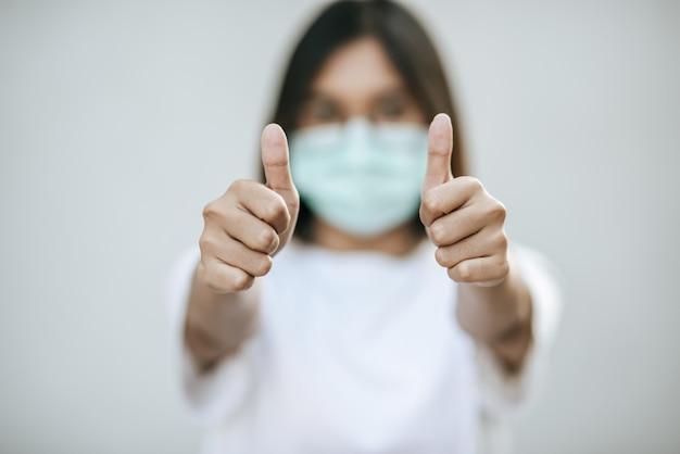 Kobiety noszą maski i zaznaczają je kciukami do góry.