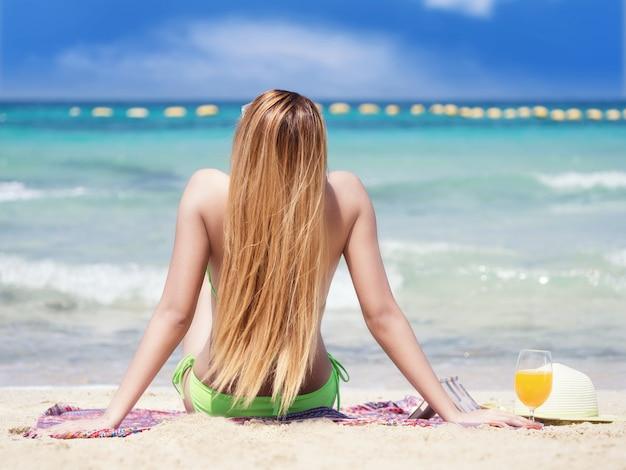Kobiety noszące bikini na plaży, siedzenia na tarasie słonecznym. relaksować się na plaży