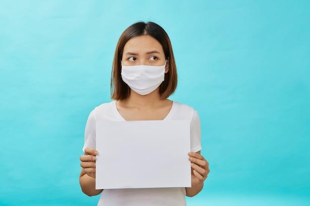 Kobiety noszące maski trzymają białą prześcieradło