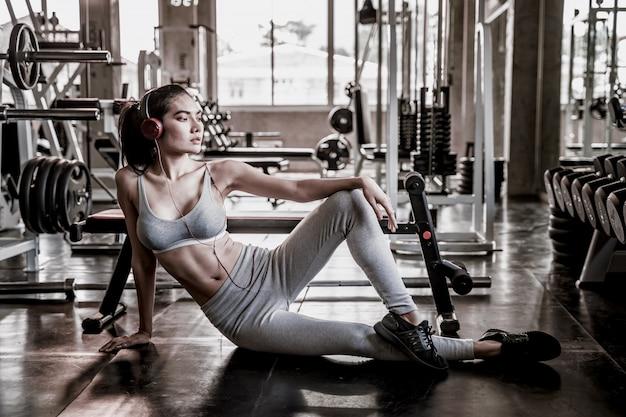 Kobiety noszące słuchawki siedzi na siłowni.