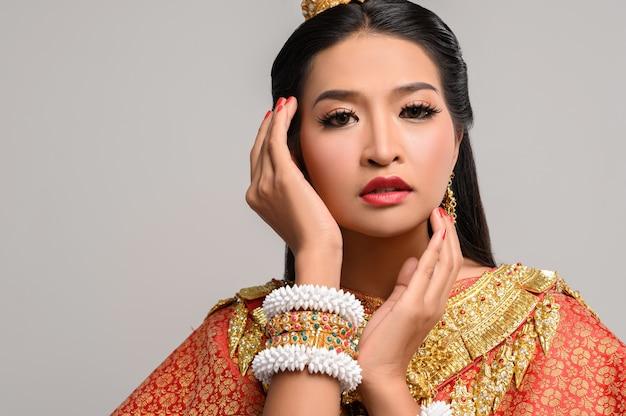 Kobiety noszące tajskie ubrania i dłonie dotykające twarzy
