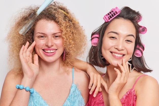 Kobiety o zdrowej skórze robią fryzurę na specjalne okazje, noszą sukienki, uśmiechając się z radością na białym tle