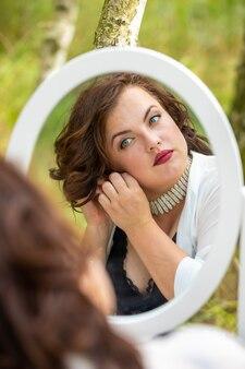Kobiety obsiadanie i patrzeć w lustrze w lesie