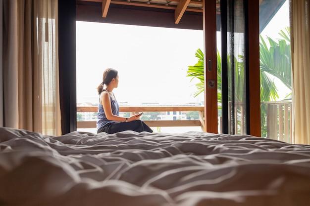 Kobiety obsiadanie na balkonowym mienia smartphone