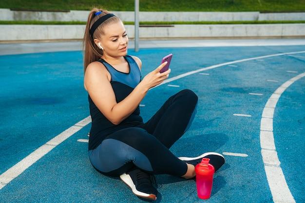 Kobiety obsiadanie na boisku z telefonem w ona ręki