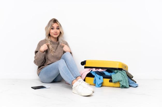 Kobiety obsiadanie na podłoga z walizką nad odosobnioną ścianą