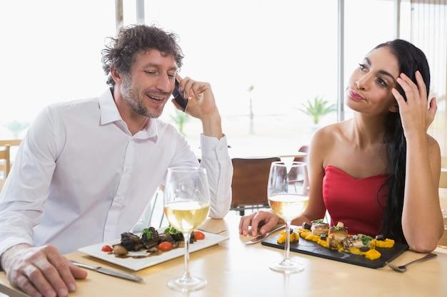 Kobiety obsiadanie podczas gdy mężczyzna opowiada telefon komórkowego
