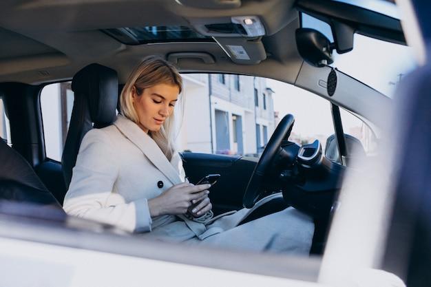 Kobiety obsiadanie wśrodku electro samochodu podczas gdy ładujący