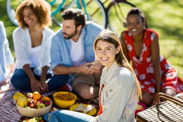 Kobiety obsiadanie z jej przyjaciółmi w parku