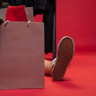 Kobiety obsiadanie z torba na zakupy między jej nogami