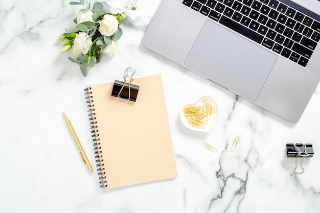 Kobiety obszar roboczy z laptopem, pamiętnikiem, bukietem kwiatów, złotymi akcesoriami