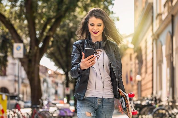 Kobiety odprowadzenie z deskorolka i smartphone
