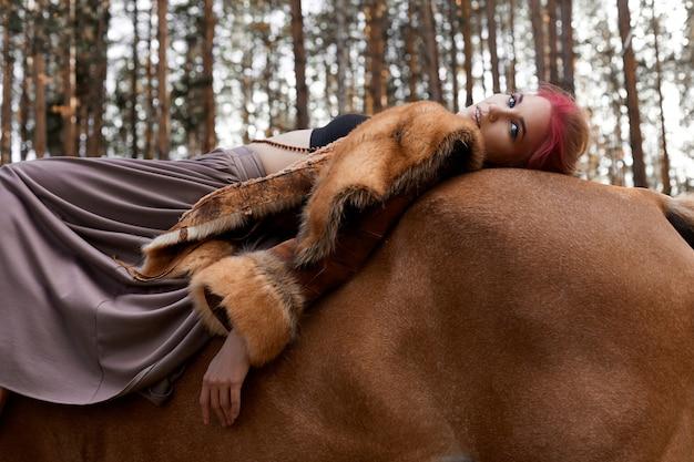 Kobiety odprowadzenie z końską jesienią na naturze. twórczy gorący różowy makijaż twarzy kobiety, farbowanie włosów. portret kobiety z koniem. jazda konna w lesie jesienią. ubrania jesienne