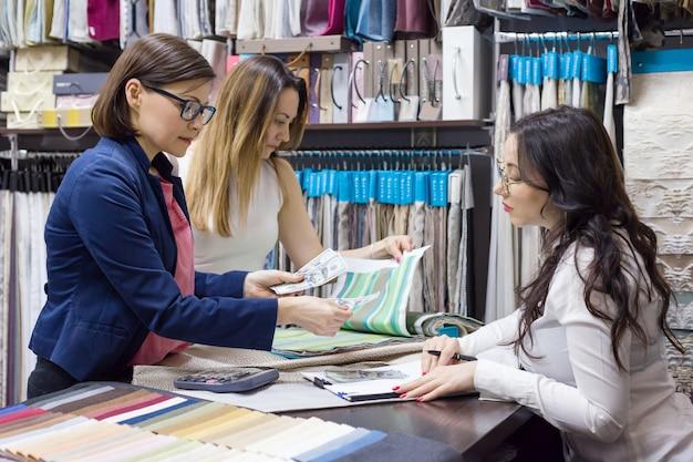 Kobiety oglądają próbki tkanin na zasłony