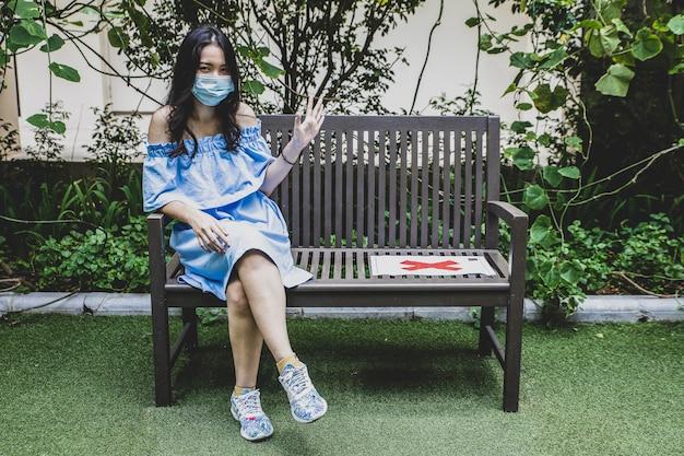 Kobiety ogólnospołeczny dystansowy obsiadanie na ławce w parku
