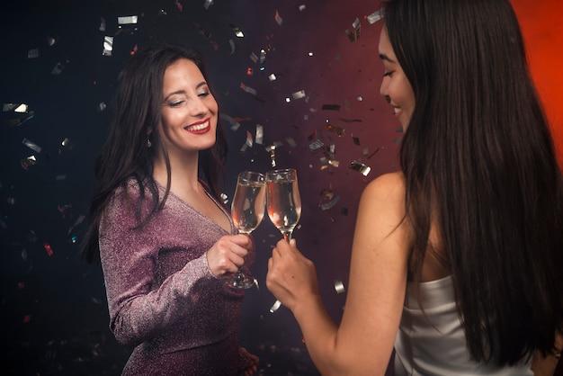 Kobiety opiekania z szampanem na imprezie noworocznej