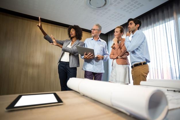 Kobiety otoczka z ręką podczas gdy stojący w deskowym pokoju z kolegami