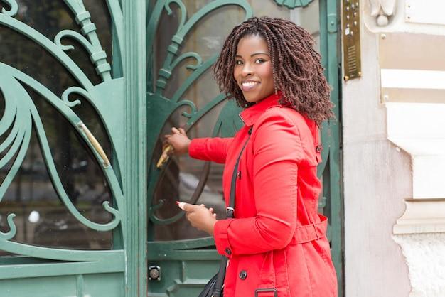 Kobiety otwarcia drzwi i ono uśmiecha się