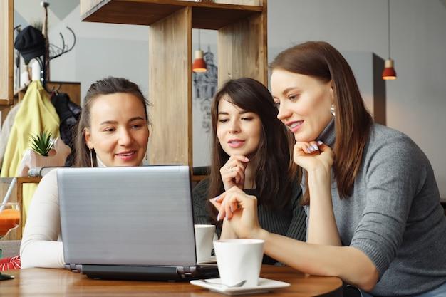 Kobiety patrząc na laptopa w kawiarni w centrum coworkingowym. spotkanie robocze