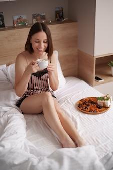 Kobiety pijące kawę z piankami na łóżku z prezentem obok niej. poranna niespodzianka